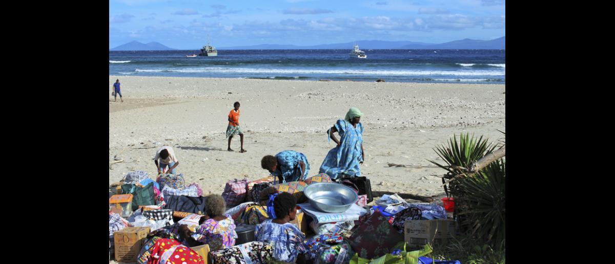 13 May 2015, Mataso island, Vanuatu: Community members rest on the beach with their belongings. © UNDP/Francisco Santos-Jara del Padron 2015