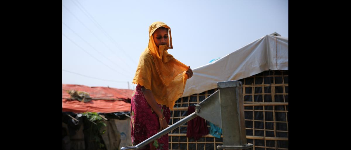 A young woman draws water at an IOM well in Kutupalong Rohingya refugee settlement in Cox's Bazar, Bangladesh.